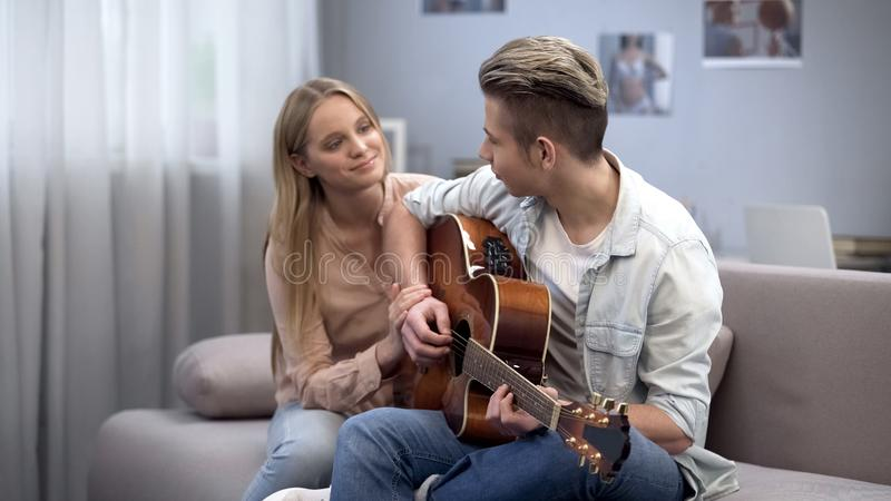 Teen student playing guitar and girlfriend hugging him, romantic love confession royalty free stock image