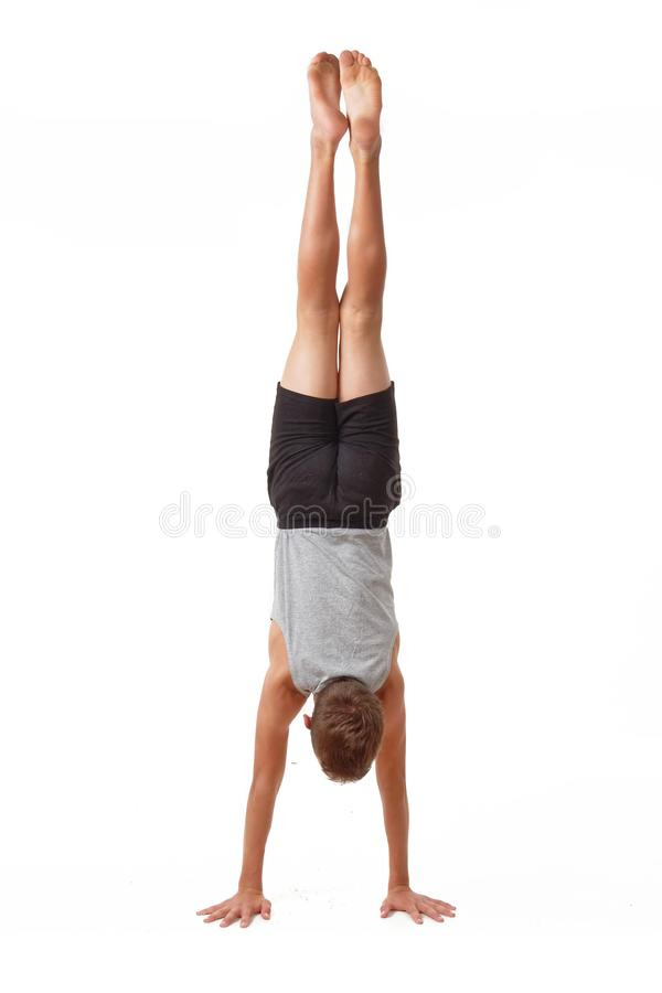 Teen in a T-shirt and shorts performs gymnastic exercises. royalty free stock image
