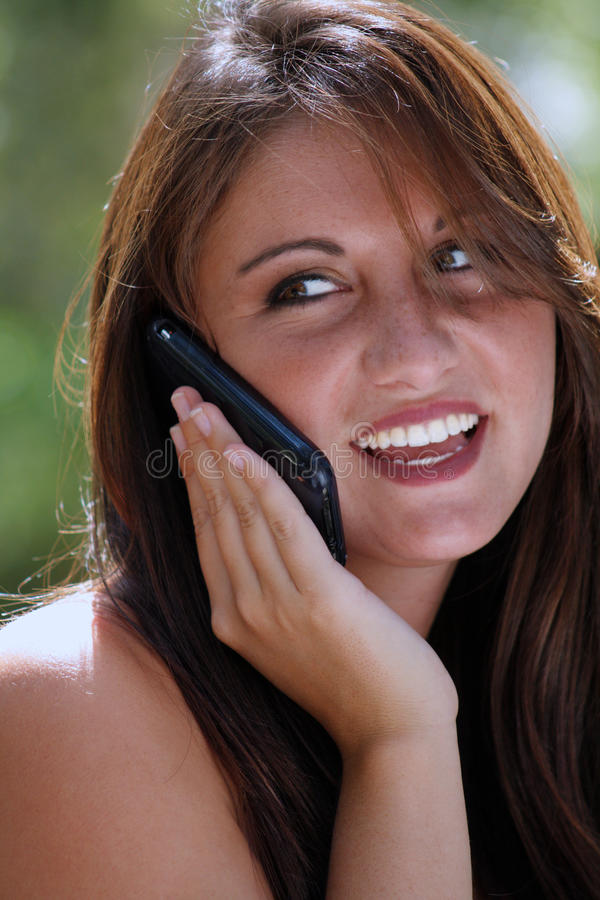 Teen Talking on Her Cell Phone Outdoors (2). A lovely teenage brunette with a bright, warm smile talking on her cell phone outdoors, looking off camera to frame royalty free stock image