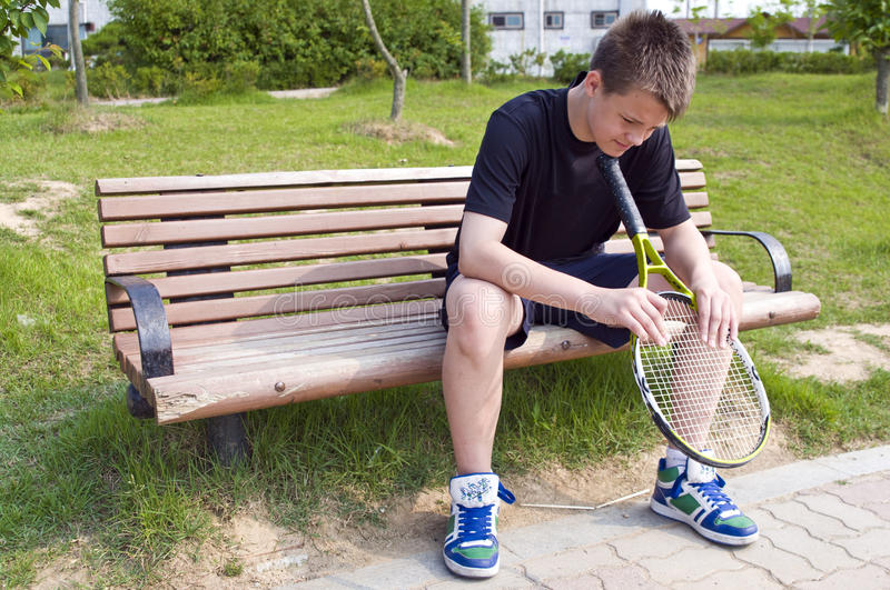 Teen tennis player. Teenage boy sitting on a bench, holding his racket stock photo