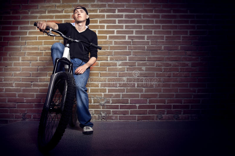 Teen thinking. About life on the background of a brick wall of the city stock photo