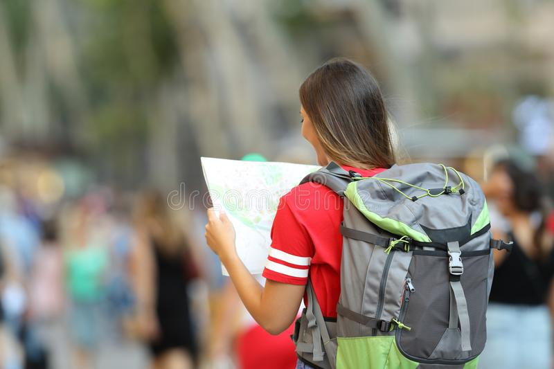 Teen tourist searching location in a paper map. Back view of a teen tourist searching location in a paper map on the street royalty free stock photo