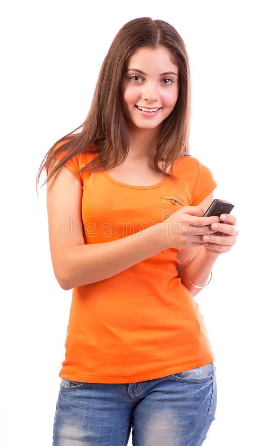 Teen using a cell phone. Beautiful girl using a cell phone isolated on white background royalty free stock image
