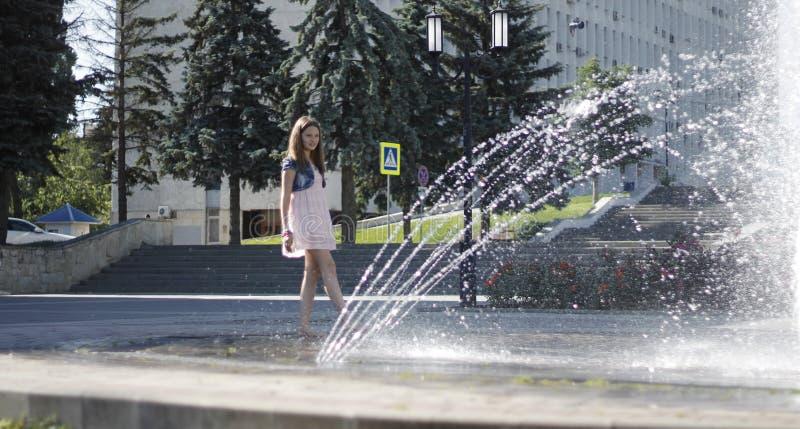 Teen vicino a una fontana splashing nel centro della città il 12 giugno 2016 a Pyatigorsk, Russia, piazza della città fotografia stock