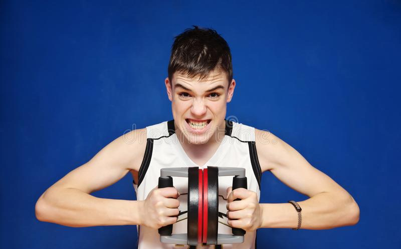 Teen violently compresses the push-UP Bars. Blue Background royalty free stock photos