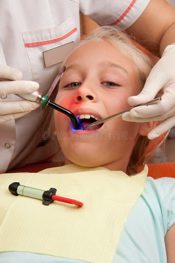 Teen visiting dentist. Teenage girl at a dentist's surgery stock photo