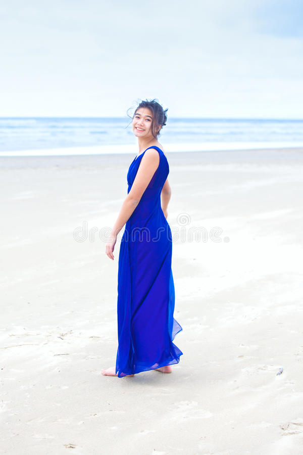 Teen wearing blue dress on beach looking back over shoulder royalty free stock images