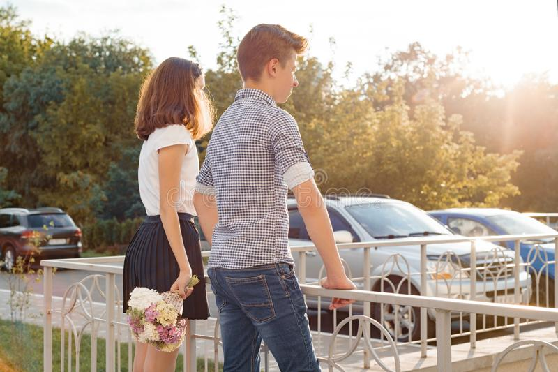 Teen youth couple boy and girl standing back, summer sunny day, girl holding bouquet of flowers in hand stock image