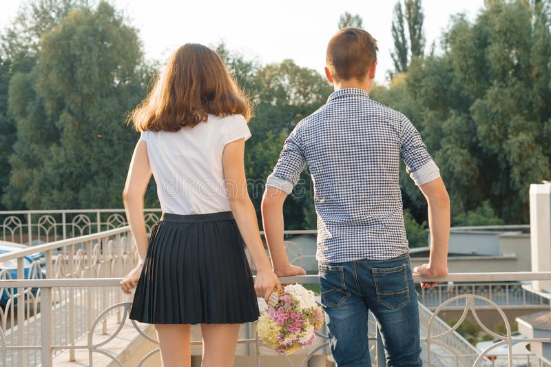 Teen youth couple boy and girl standing back, summer sunny day, girl holding bouquet of flowers in hand royalty free stock photo