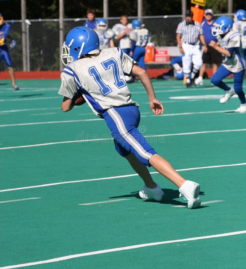 Teen Youth Football Player Running with the Ball stock images