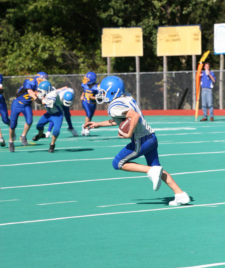 Teen Youth Football Player Running with the Ball stock photography