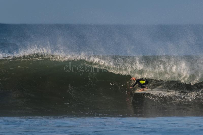 Teen youth showing bravery on large wave. royalty free stock image