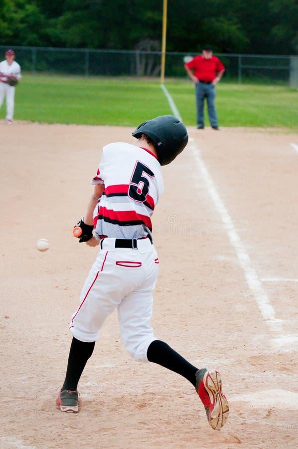 Youth baseball batter hitting ball. stock photo