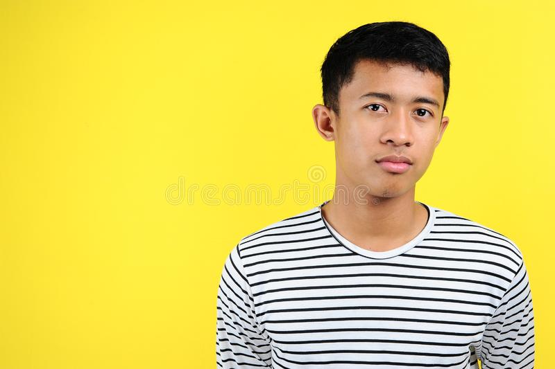 Teenage Asian boy with serious expression, head and shoulders stock image