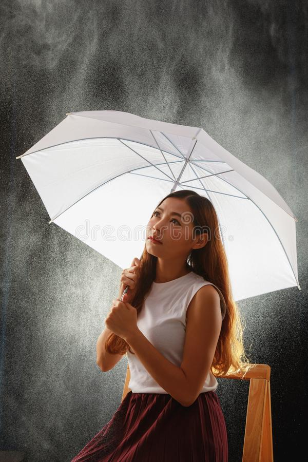 Teenage Asian girl holding umbrella and sitting while rainy royalty free stock photos