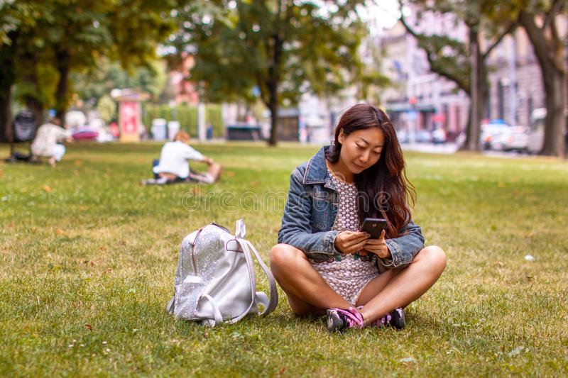 Teenage girl laying in park using mobile phone. Teenage asian girl laying in park using mobile phone in autumn royalty free stock photo