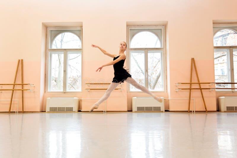 Teenage ballerina practicing ballet moves in large dancing studio stock photo