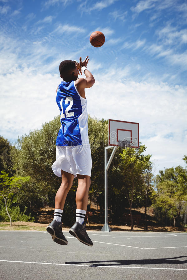 Teenage basketball player scoring while practicing in court. On sunny day stock images