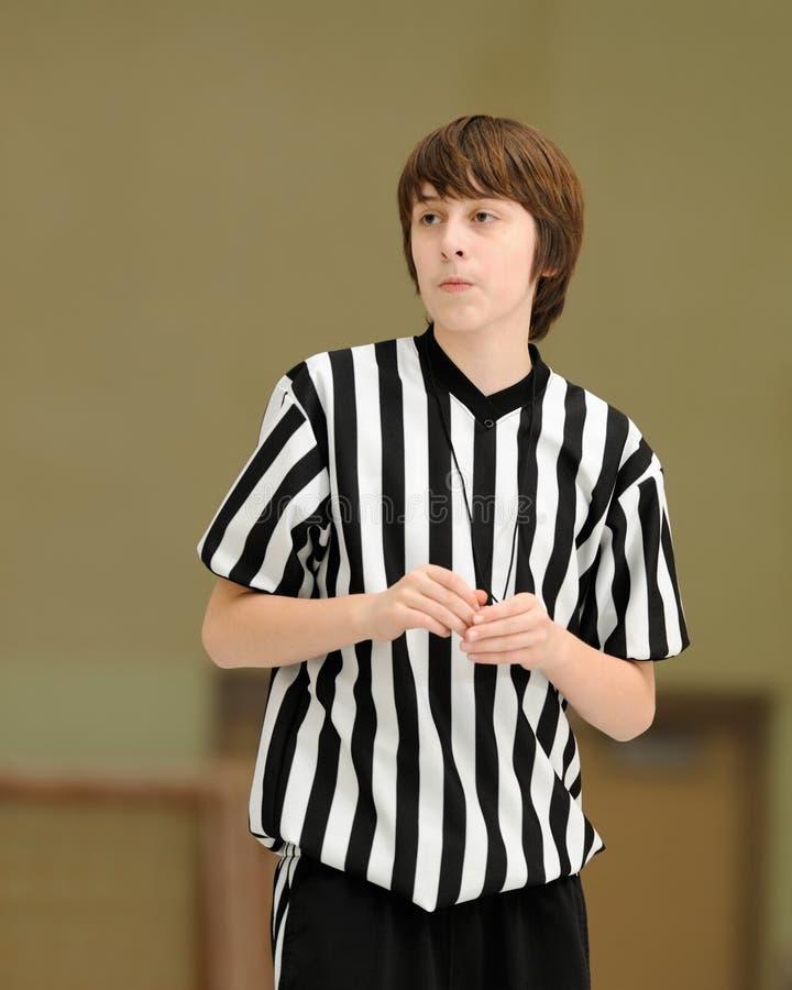 Teenage basketball referee. Teenage caucasian boy referees basketball game in gymnasium royalty free stock photos