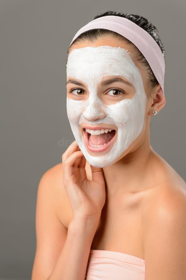 Teenage beauty smiling girl white facial mask stock image