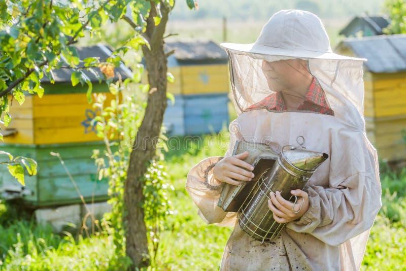 Teenage beekeeper and beehive on bee yard. Teenage beekeeper and beehive on village bee yard royalty free stock photo