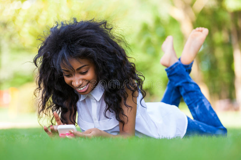 Download Teenage Black Girl Using A Phone, Lying On The Grass - African P Stock Photo - Image: 32918110