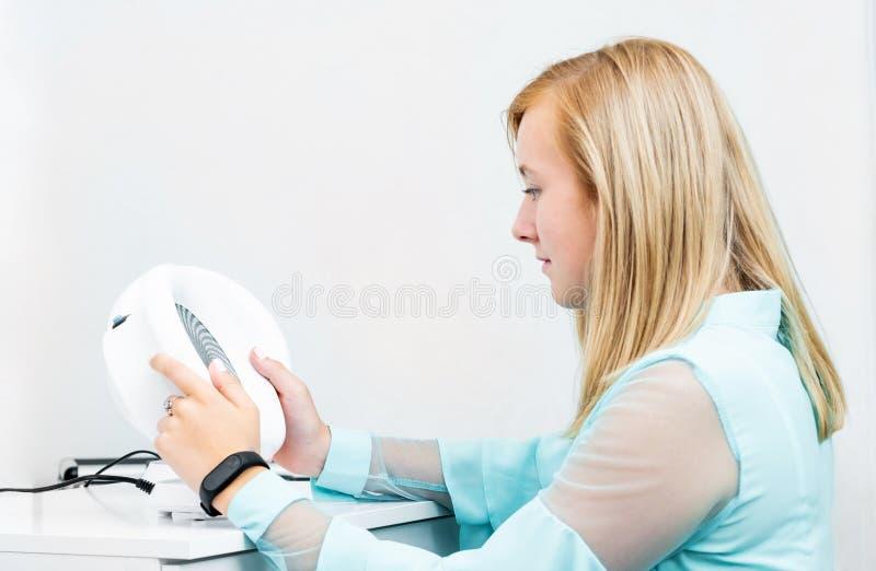 Teenage blond girl udergoes eye survey in ophthalmologic clinic stock images
