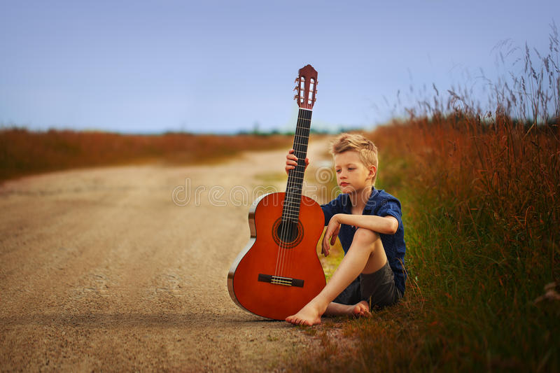 Teenage boy with acoustic guitar on country road. stock photography