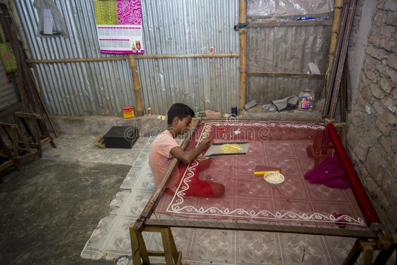 A teenage boy adds detail to a traditional Jamdani saree in Mirpur Benarashi Palli, Dhaka, Bangladesh. During partition in 1947 some 125 families migrated to royalty free stock photography