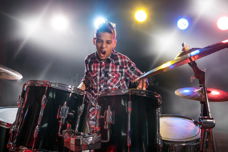 Teenage boy behind drum kit. Boy, learn to play drums royalty free stock image