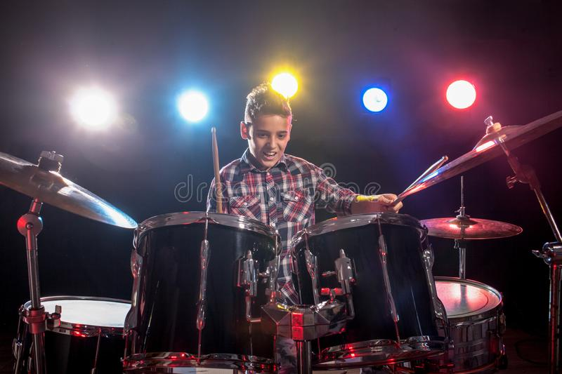 Teenage boy behind drum kit. Boy, learn to play drums stock photo