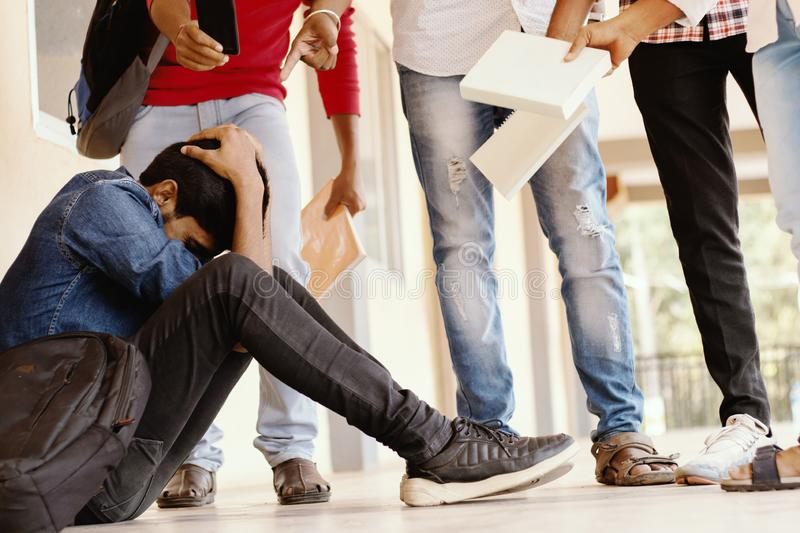 Teenage Boy Being Bullied At School, covered his face - group of students threatening to hit classmate or junior at. University - Concept of teasing, bulling or stock photos