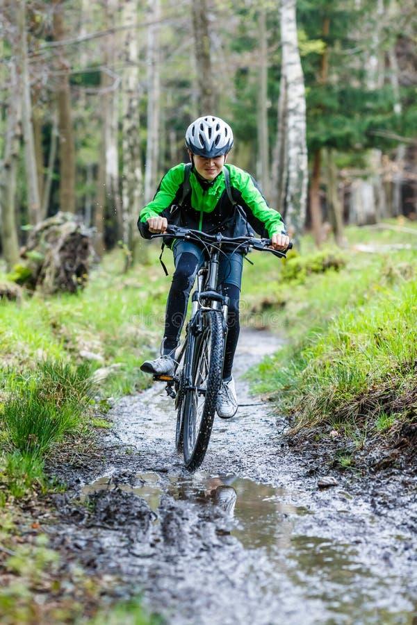 Teenage boy biking on forest trails stock images