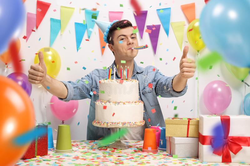 Teenage boy with a birthday cake and a party horn royalty free stock photos
