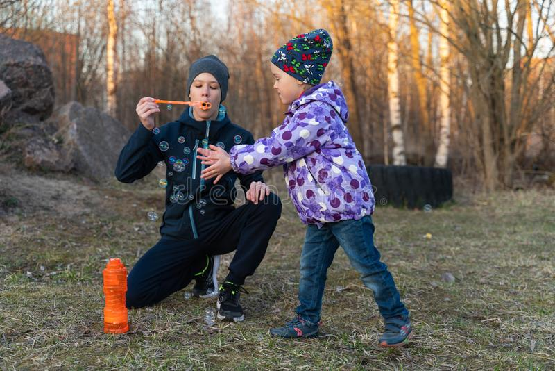 A teenage boy in a blue jacket and a gray hat and a girl blowing bubbles in the open air. children`s portrait royalty free stock image