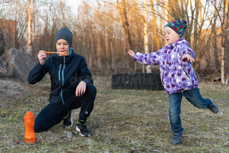 A teenage boy in a blue jacket and a gray hat and a girl blowing bubbles in the open air. children`s portrait royalty free stock photo