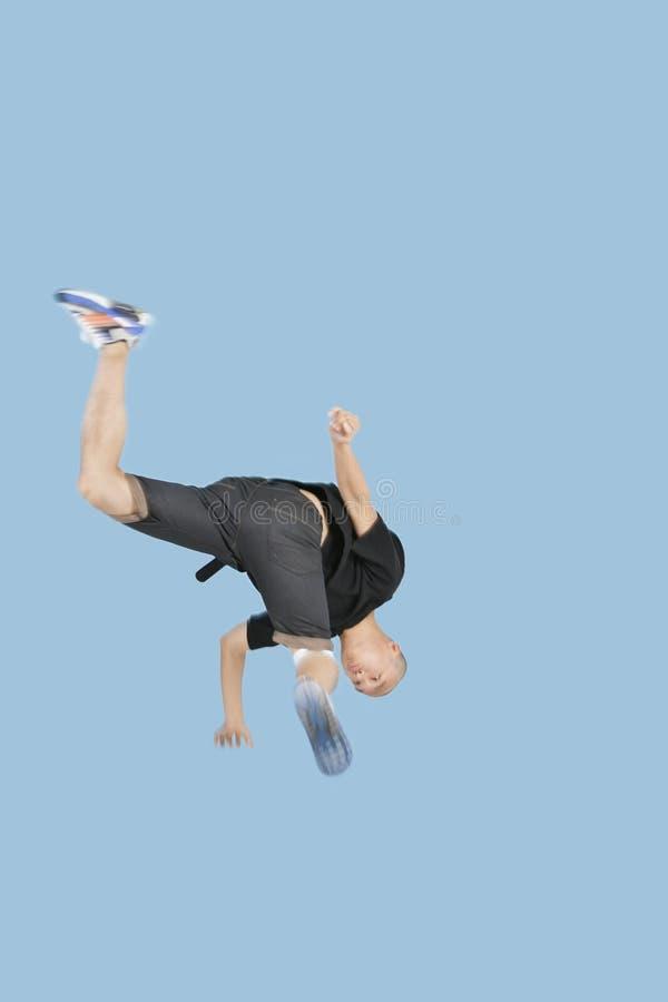 Teenage boy break dancing over blue background stock photography
