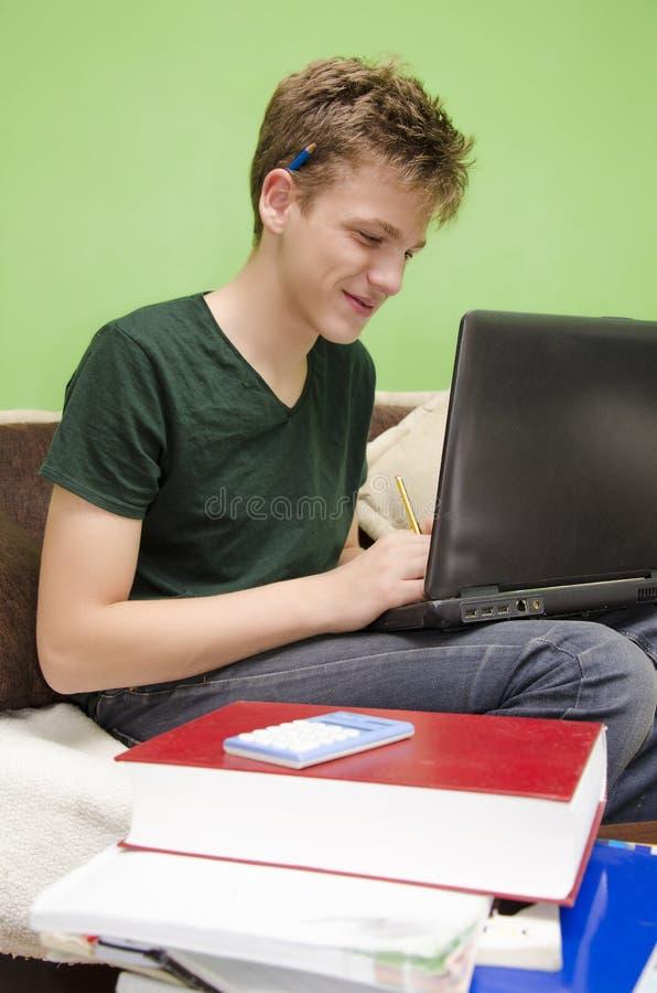 Teenage boy doing homework on laptop stock photography