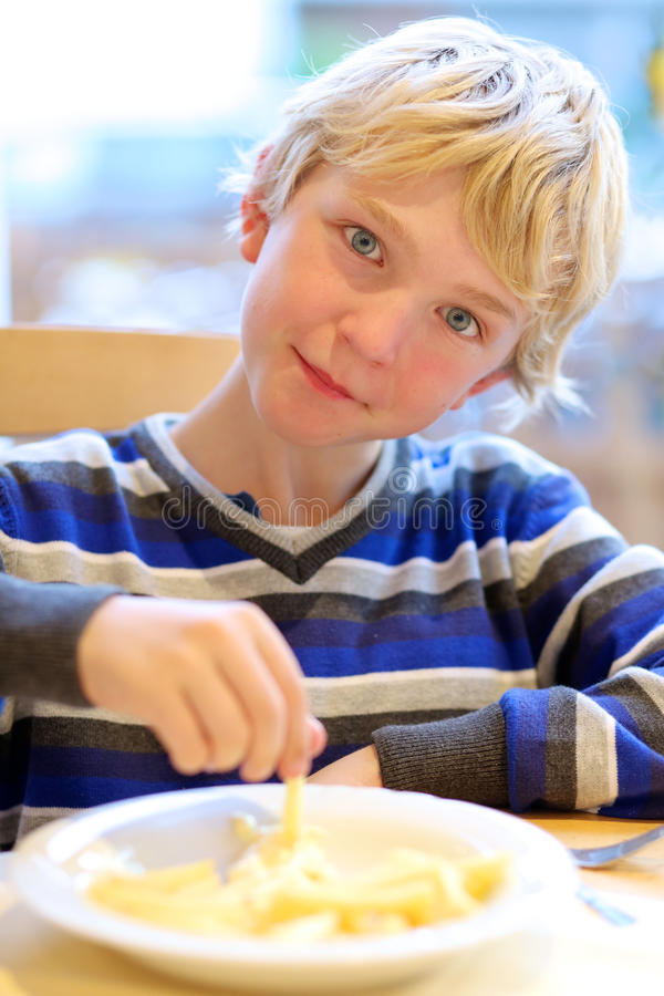 Teenage boy eating fried potato stock photo