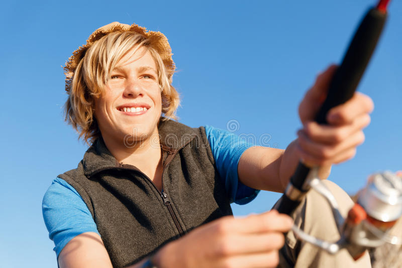 Teenage boy fishing at sea royalty free stock image