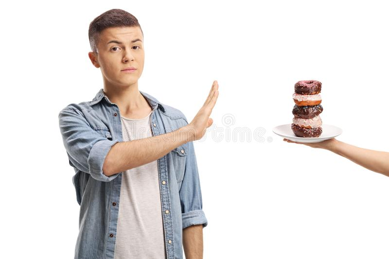 Teenage boy gesturing stop with his hand to a pile of donuts on royalty free stock photos