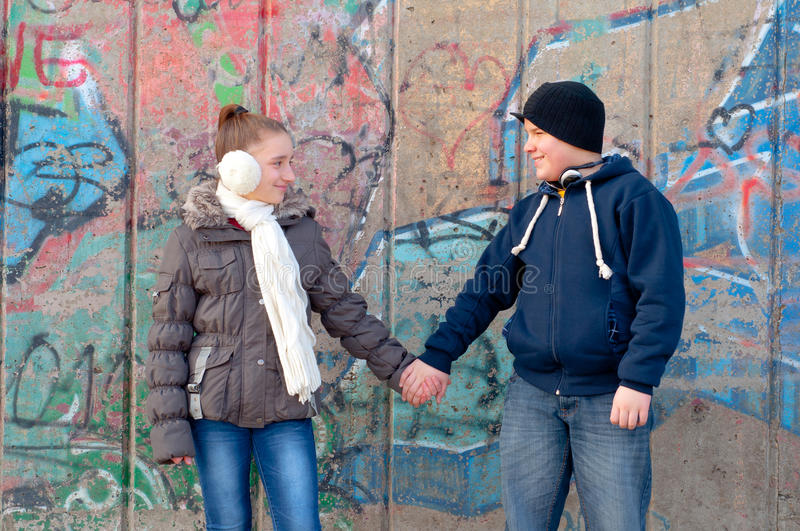 Teenage boy and girl holding hands and smiling royalty free stock photos