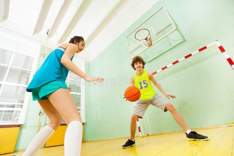 Teenage boy and girl playing basketball in gym. Bottom view portrait of teenage boy and girl playing basketball in gymnasium royalty free stock photography