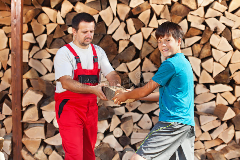 Teenage boy helping father stack the firewood royalty free stock photos