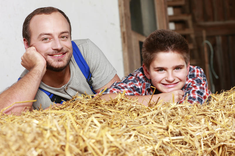 Teenage boy and his father lying on a straw bale stock image