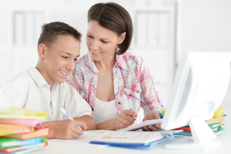 Portrait of Teenage boy doing homework with computer royalty free stock photo