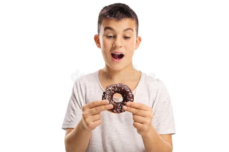 Teenage boy holding a chocolate donut about to bite it stock images
