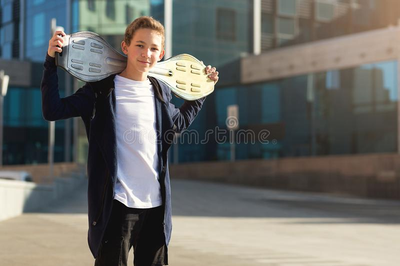 Teenage boy holding skateboard outdoors, standing on the street and looking at camera. Copy space royalty free stock photography