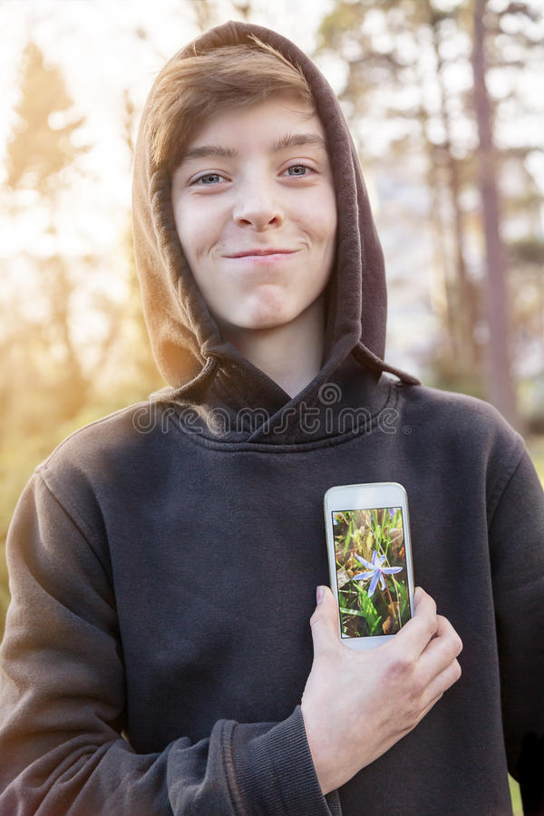 Teenage boy holding a smart phone in front of his heart stock photography