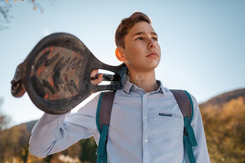 A teenage boy holds a skateboard in his hands and looks away. Mountains and sky in the background. Bottom view royalty free stock image